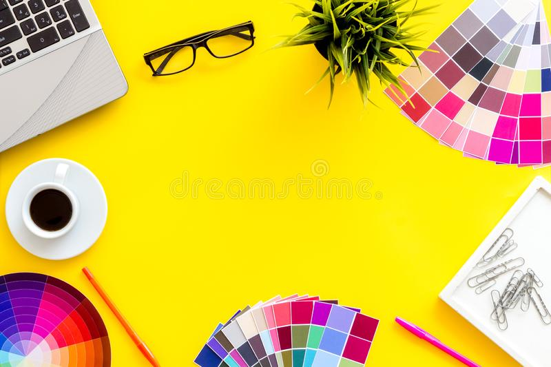 Pallet, laptop, glasses, cup of coffee and tools for designer work on yellow desk background top view copyspace frame royalty free stock photo