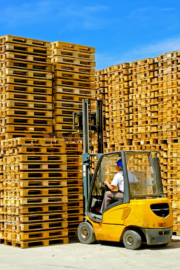 Pallets forklift. Forklift operator lifting bunch of wooden pallets stock photo