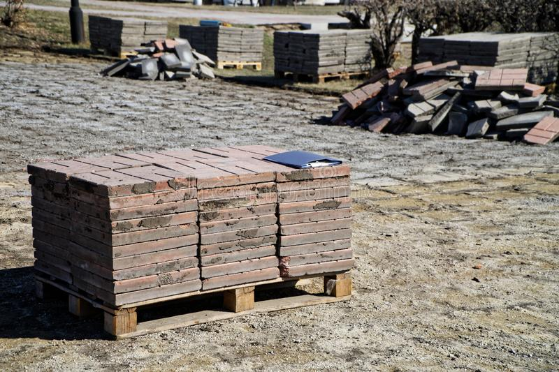 Pallets with paving slabs during its dismantling on a city street. Urban economy royalty free stock image