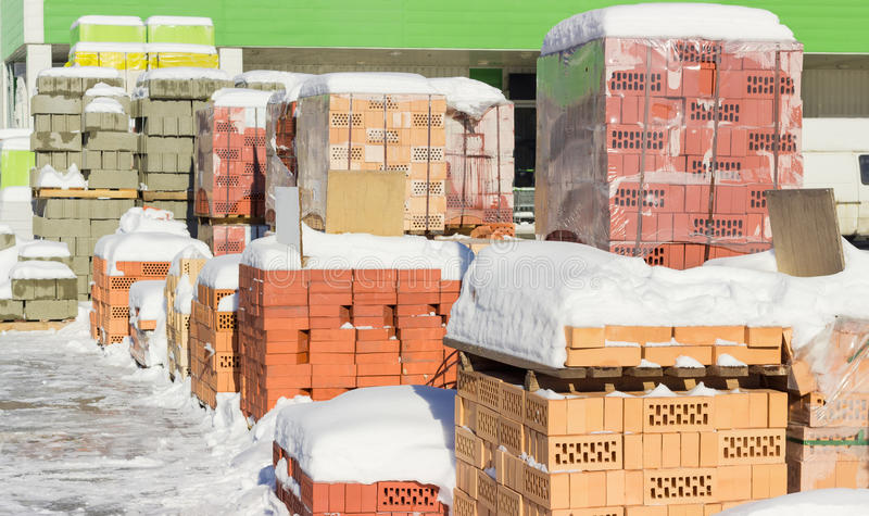 Pallets with red bricks and concrete masonry units on warehouse. Pallets with different red bricks and concrete masonry units covered snow on an outdoor stock images