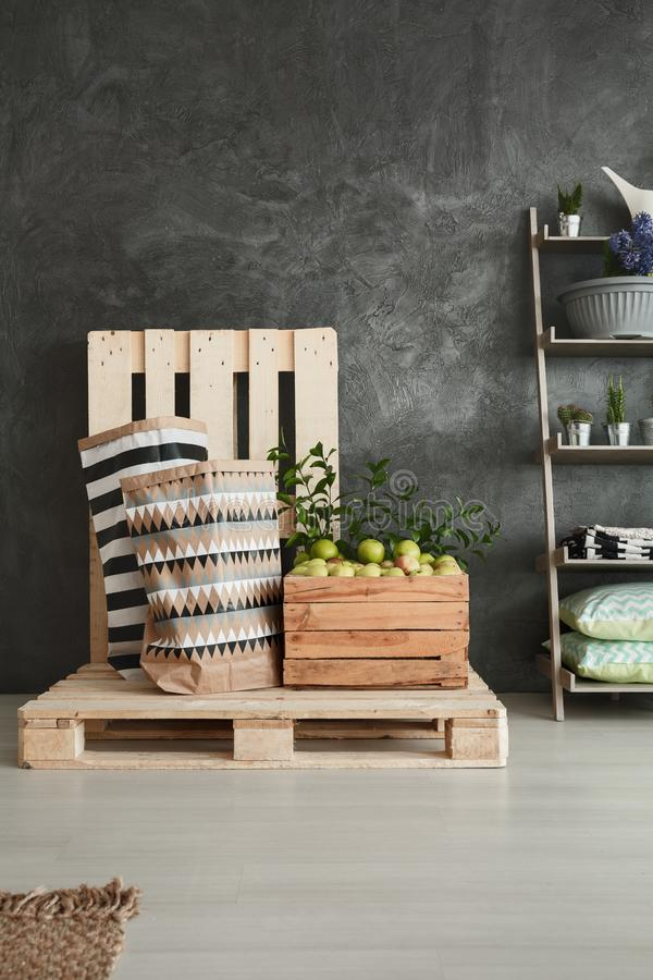 Pallets in storage. Wooden pallets with box of apples in modern grey home storage stock photo