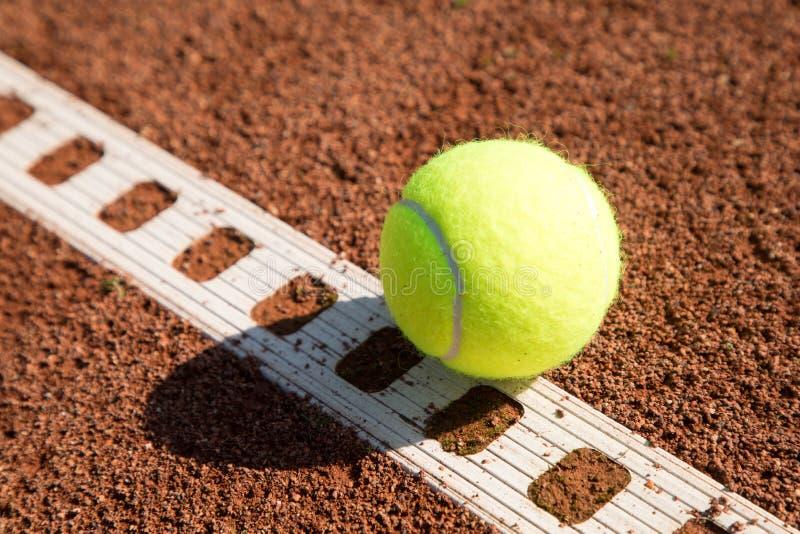 Pallina da tennis con la linea su una corte della sabbia immagine stock