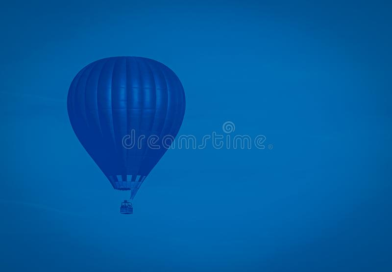 Palloncino classico blu ad aria calda che vola nel cielo, tonato immagini stock libere da diritti