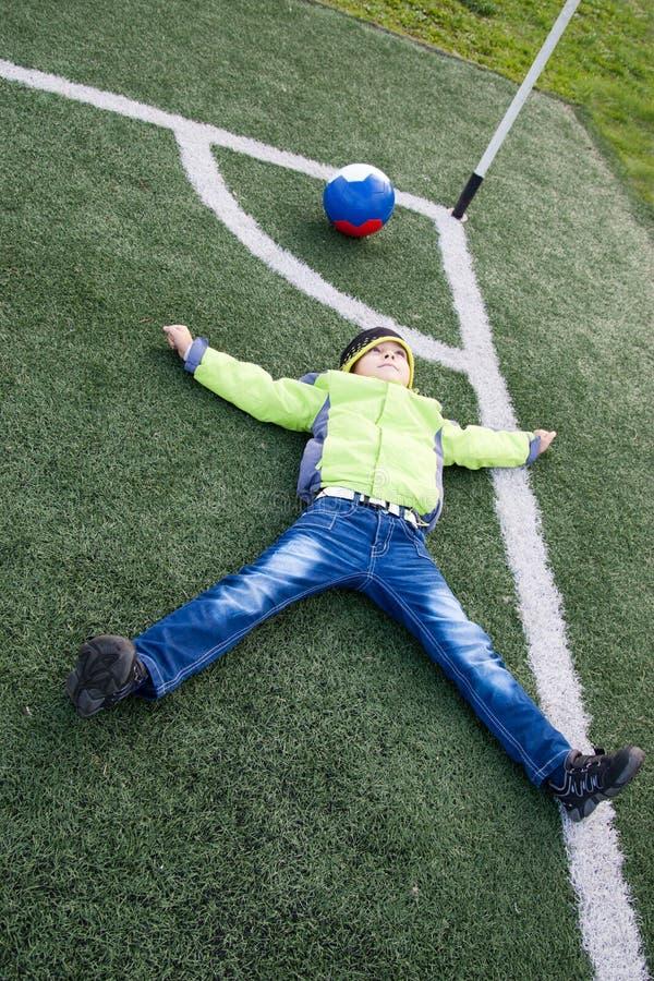 Pallone da calcio del ragazzino che si trova sull'erba fotografia stock