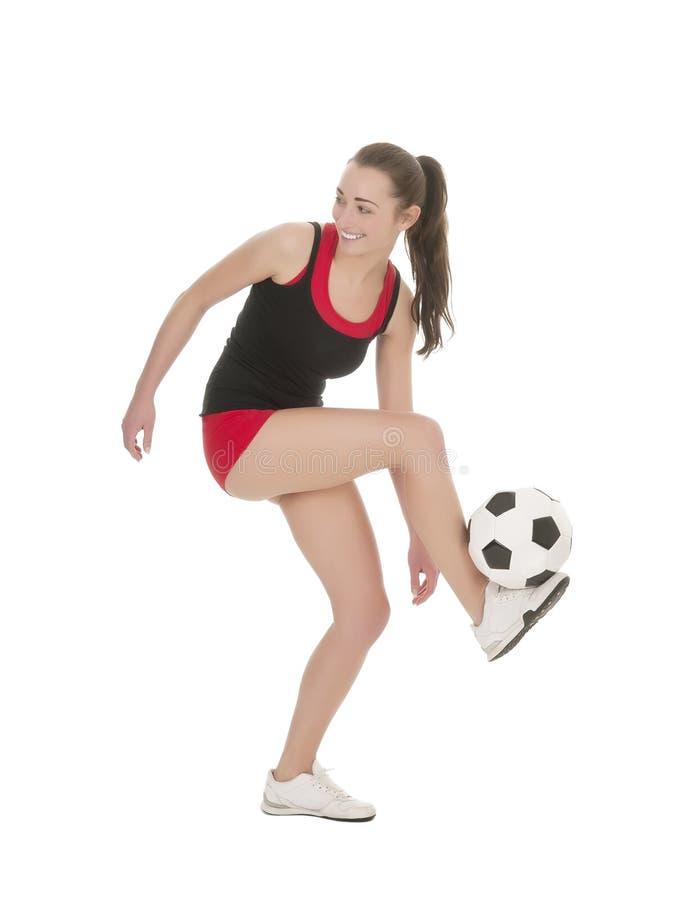 Pallone da calcio di manipolazione della donna sportiva fotografia stock