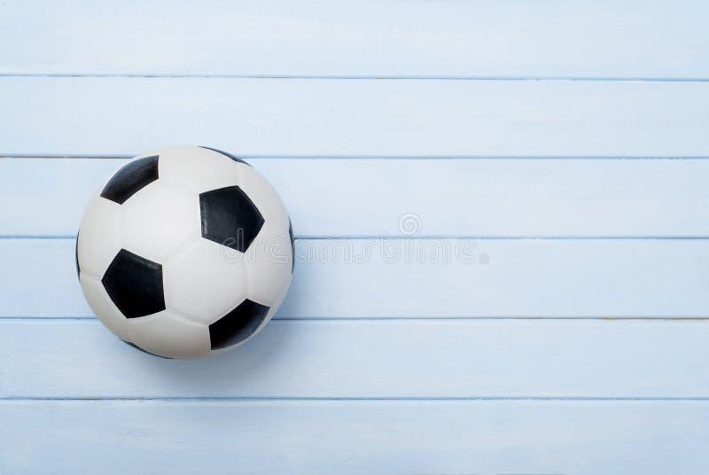 Pallone da calcio o calcio sul pavimento di legno blu fotografie stock libere da diritti