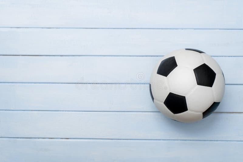Pallone da calcio o calcio sul pavimento di legno blu immagine stock libera da diritti