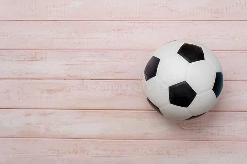 Pallone da calcio o calcio sul pavimento di legno rosa immagine stock
