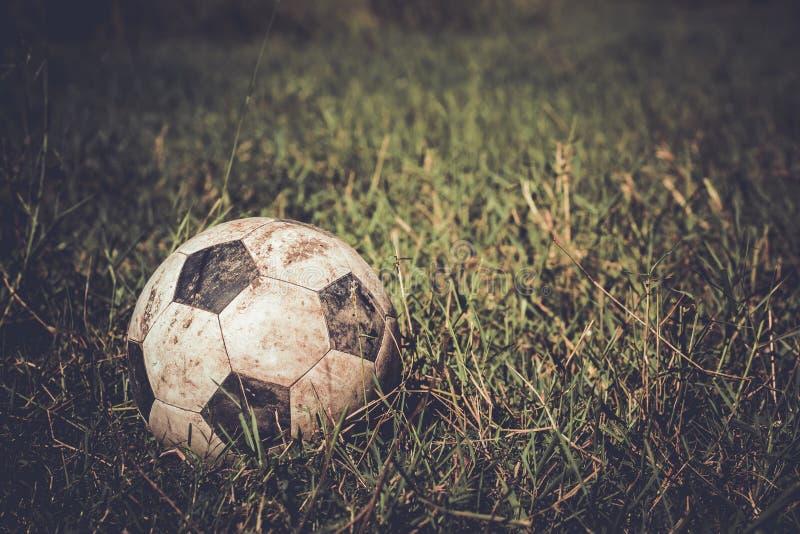 Pallone da calcio sporco su erba fotografia stock