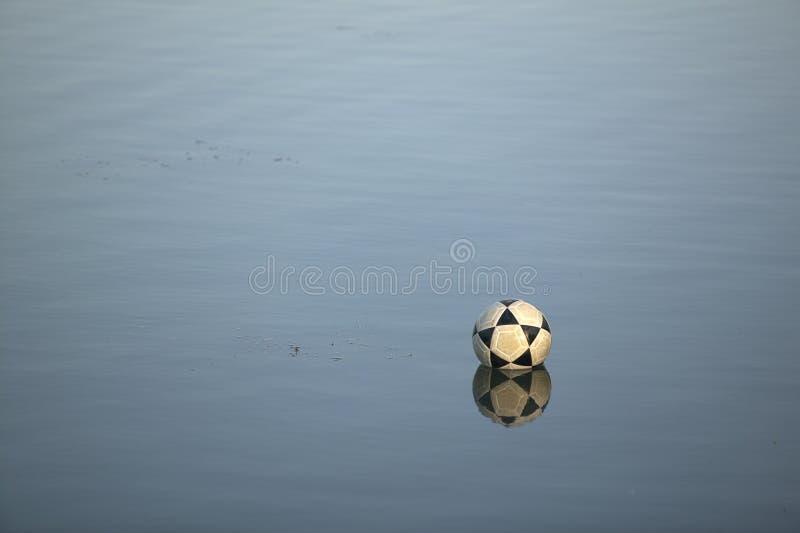 Pallone da calcio su acqua immagine stock
