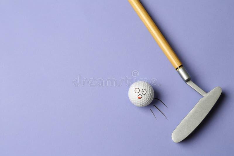 Pallone da golf con faccia divertente che vola via dal club su sfondo lilla - immagine creativa immagini stock