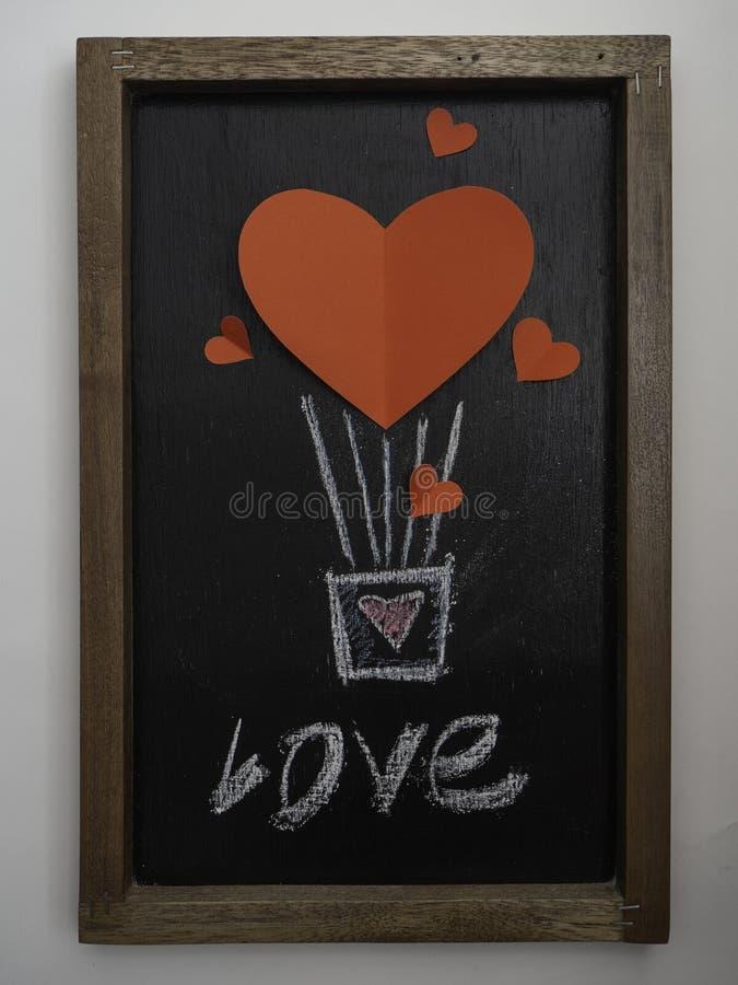 Pallone rosso del cuore per la lavagna di giorno di biglietti di S. Valentino fotografie stock
