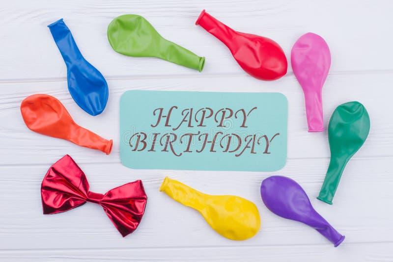 Palloni assortiti e biglietto di auguri per il compleanno felice immagine stock