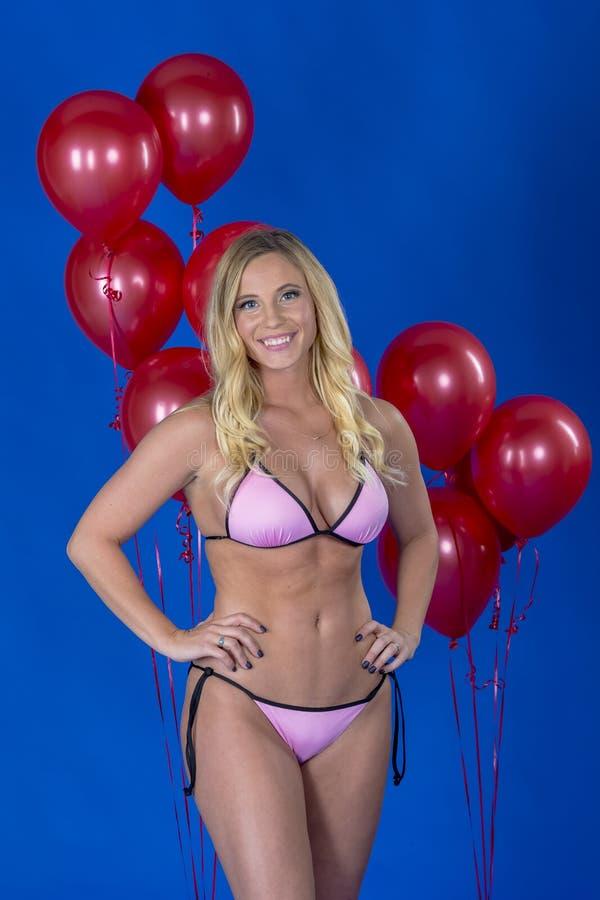 Palloni biondi adorabili di Posing Against Red del modello del bikini in un ambiente dello studio fotografie stock libere da diritti