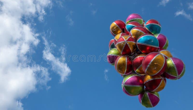 Palloni brillanti variopinti con le bande bianche e aree colorate davanti ad un cielo blu quasi senza nuvole fotografia stock libera da diritti