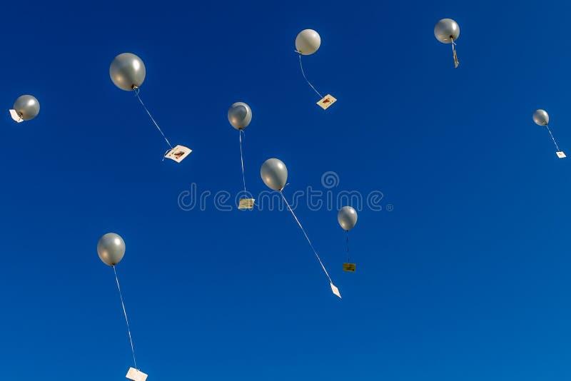Palloni d'argento che vanno su nel cielo blu fotografia stock