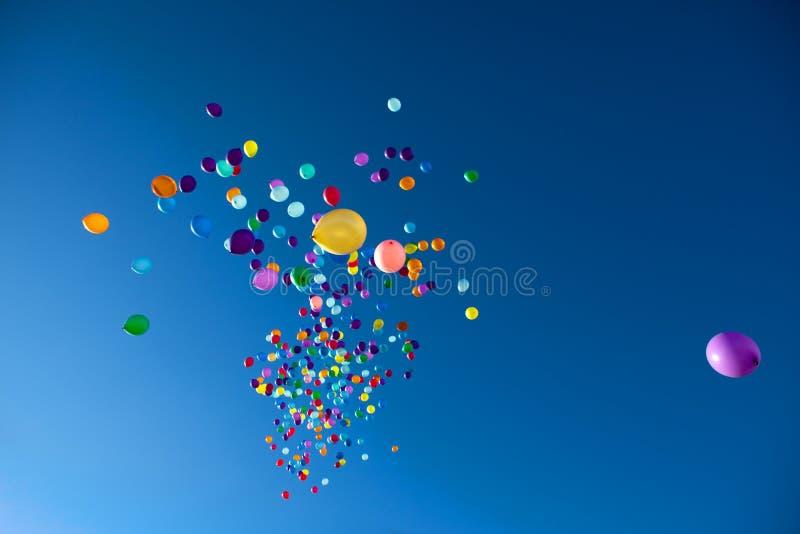 Palloni variopinti che volano nel partito del cielo fotografia stock