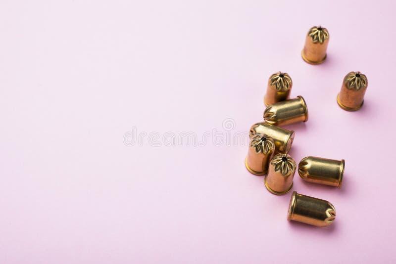 Pallottole d'annata dell'oro su un fondo rosa, spazio per testo fotografia stock libera da diritti