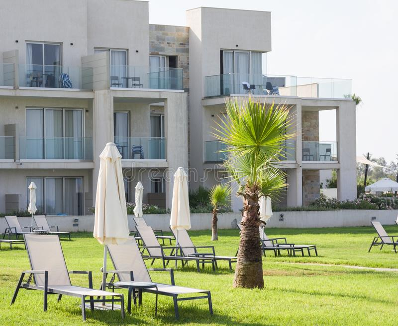 Palm Beach avec des lits pliants vides contre Constantinou Bros Athena Beach Hotel L'hôtel était entièrement au sujet de images libres de droits