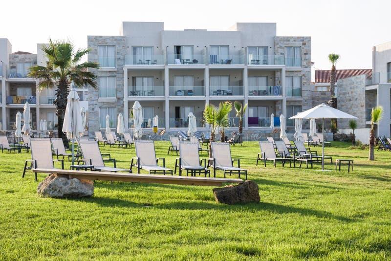 Palm Beach avec des lits pliants vides contre l'hôtel d'amphore photographie stock libre de droits