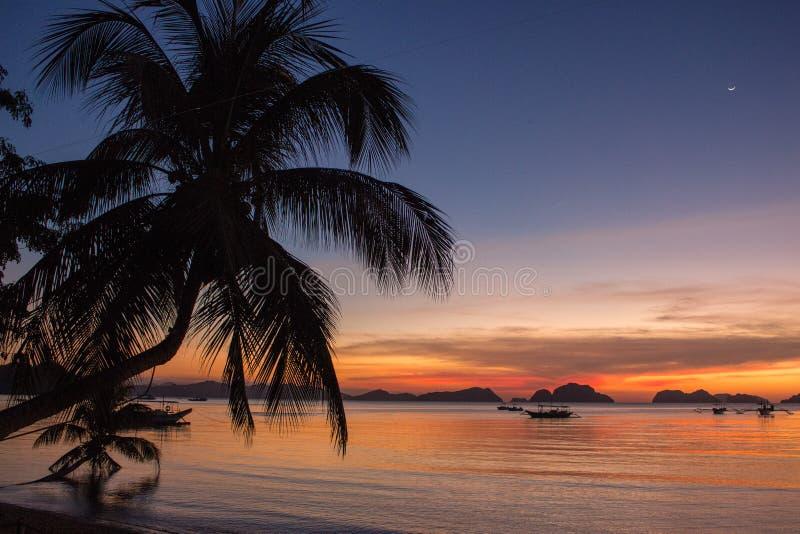 Palm en botensilhouetten op de heldere achtergrond van de zonsonderganghemel Toneelzonsondergang op tropisch strand met bergen op royalty-vrije stock afbeeldingen