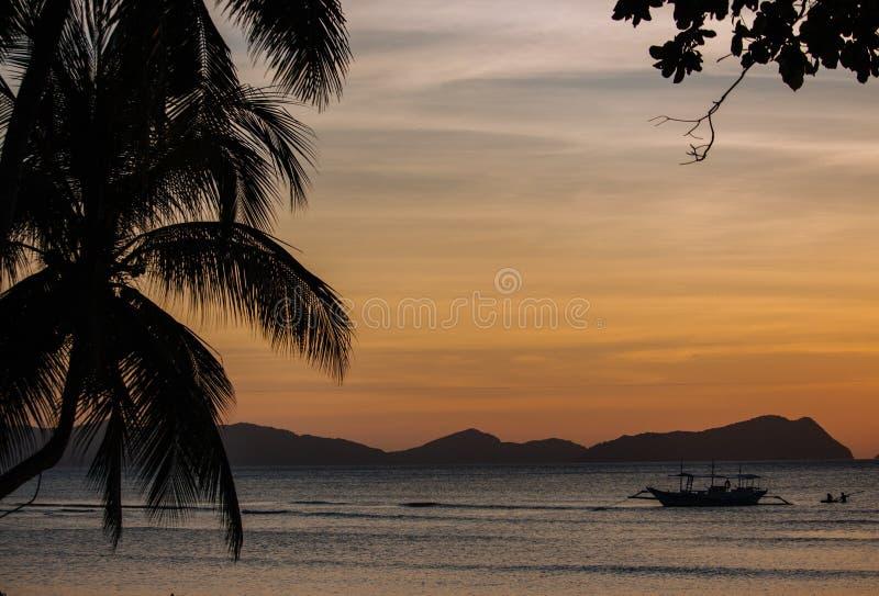 Palm en botensilhouetten op de heldere achtergrond van de zonsonderganghemel Toneelzonsondergang op tropisch strand met bergen op stock foto