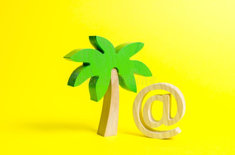 Palm figurine and symbol of internet or email. Remote work, part-time job. Outsourcing services. Work during vacation or travel stock images