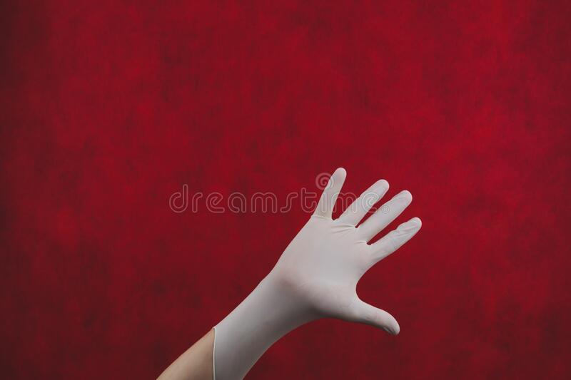 Palm of hand in medical glove on a red background. gesturing hand in white protective glove royalty free stock photo