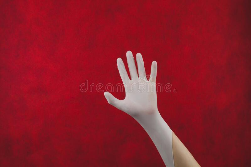 Palm of hand in medical glove on a red background. gesturing hand in white protective glove stock image