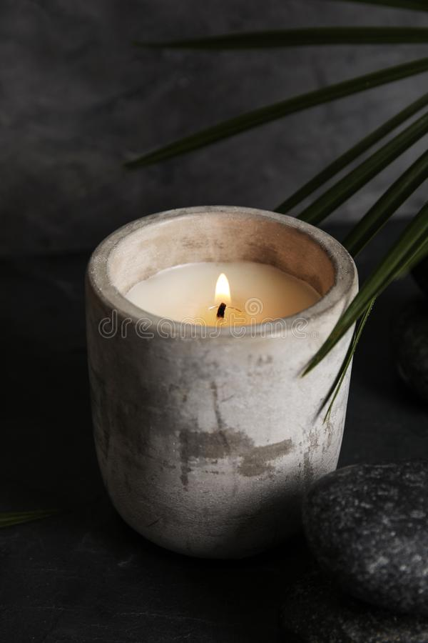 Palm leaf near burning candle and spa stones on table stock image
