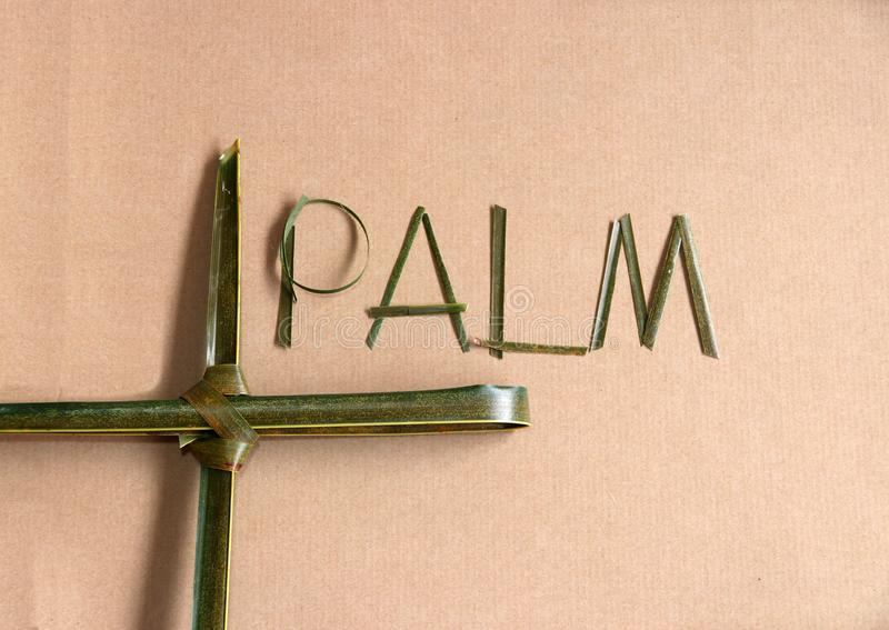 """Palm leaf set cross to crucifix with palm leaf set to the word """"palm"""" on the brown paper background. stock image"""