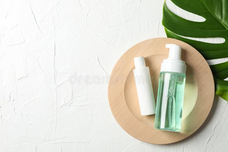 Palm leaf, wood plate, bottles with scrub and cream on white background. Copy space stock photo