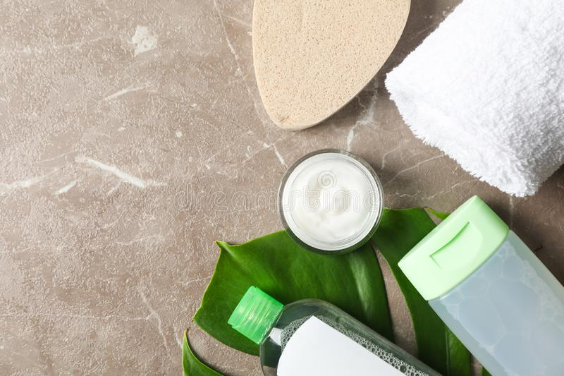 Palm leaves, cream, sponge, shower gel, shampoo and towel. Space for text royalty free stock photos