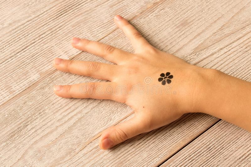 Palm of little girl with baby tattoo on wooden background royalty free stock images