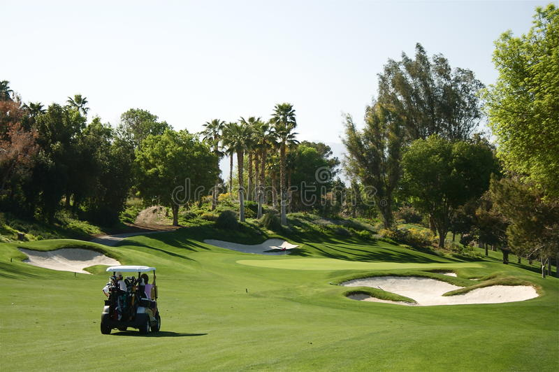 Palm Springs golf cart riders. A golf cart rides down the fairway in Palm Springs royalty free stock image