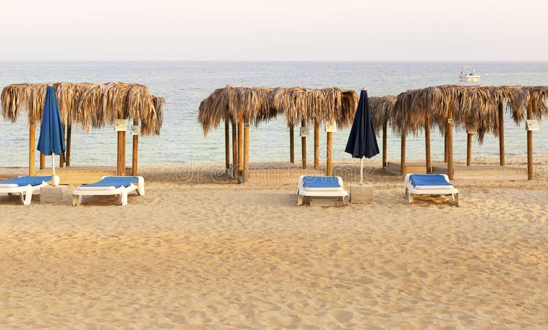 Palm thatch bed shade on the sand beach. Palm thatch bed shade on the beach ready for summer season stock image