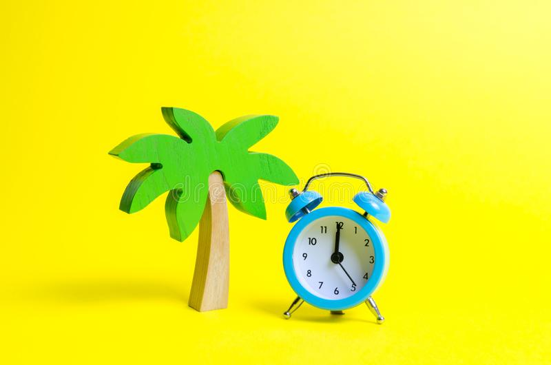 Palm tree and blue alarm clock on a yellow background. Time for rest and relaxation. Travel, vacation, cruise. Tourism stock photo
