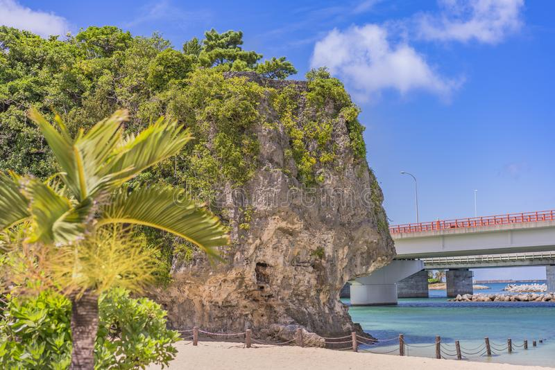 Palm tree on the sandy beach Naminoue topped by a huge rock with a Shinto Shrine at the top of a cliff and a highway passing in stock photos
