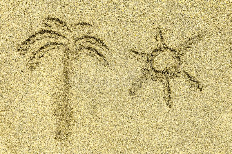 Palm tree and sun simple signs on sunny sea san. Palm tree and sun simple signs on bright sunny sea sand royalty free stock photo