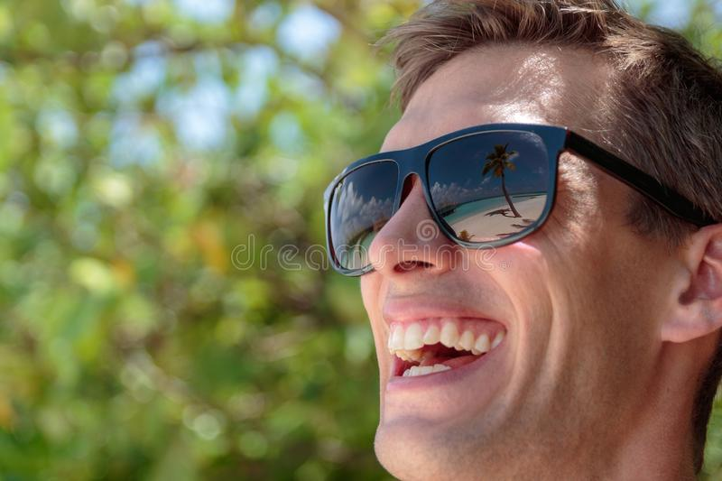 Palm tree, white beach and crystal clear blue water reflected in the sunglasses of a happy man. Maldives stock photography