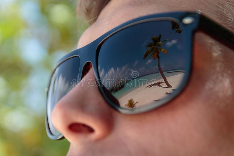 Palm tree, white beach and crystal clear blue water reflected in the sunglasses of a man. Maldives. Close-up of boy face reflecting a tropical destination in his royalty free stock photo