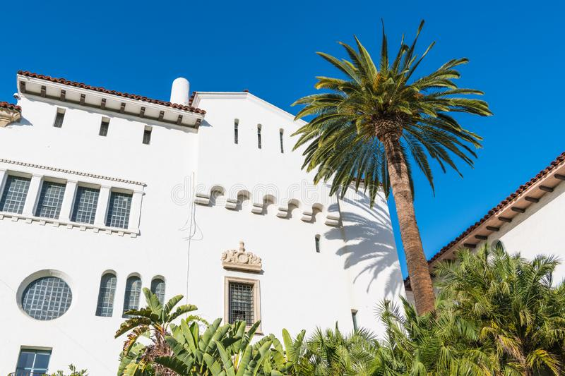A palm tree and a white Spanish architecture style building with ornate windows and trim under a beautiful blue sky stock photography