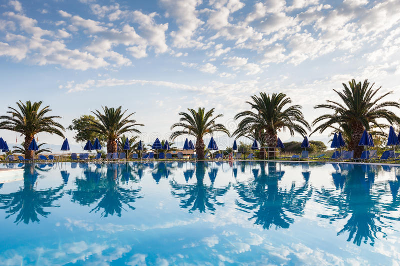 Palm trees, beach sunbeds and umbrellas near the pool by the sea royalty free stock photography