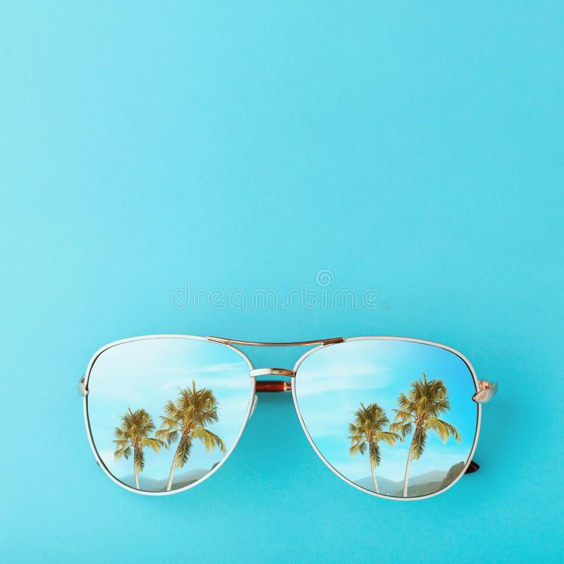Palm trees and mountains are reflected in sunglasses. Concept on the theme of vacation and travel with copy space stock photo