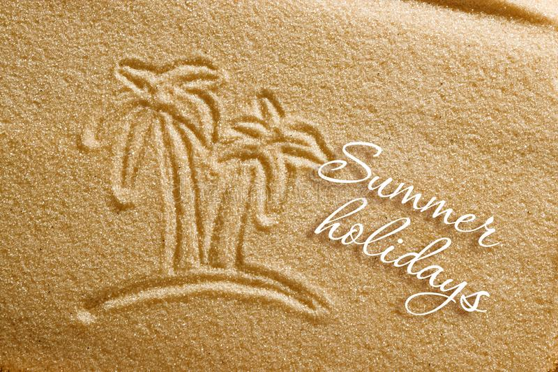 Palm trees are painted in the sand and the inscription is summer holidays. Beach background. View from above. The concept of stock photos