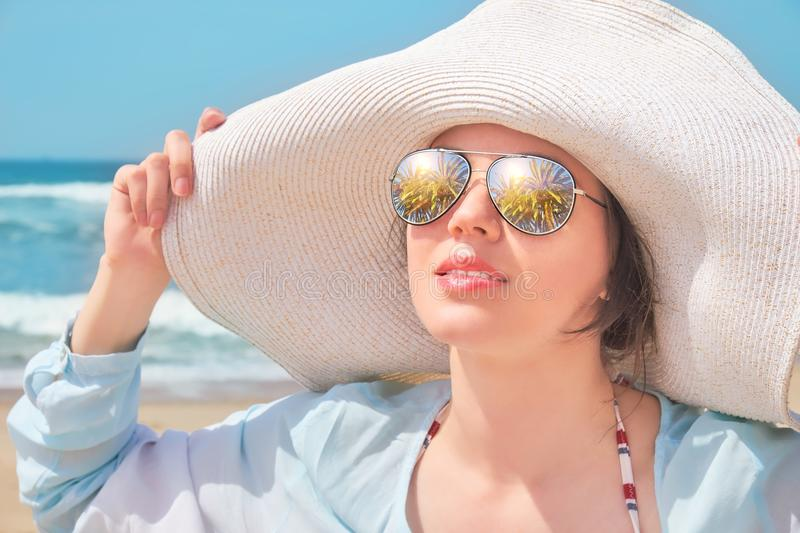 Palm trees reflect in the sunglasses, Portrait of a woman in hat on summer beach royalty free stock image