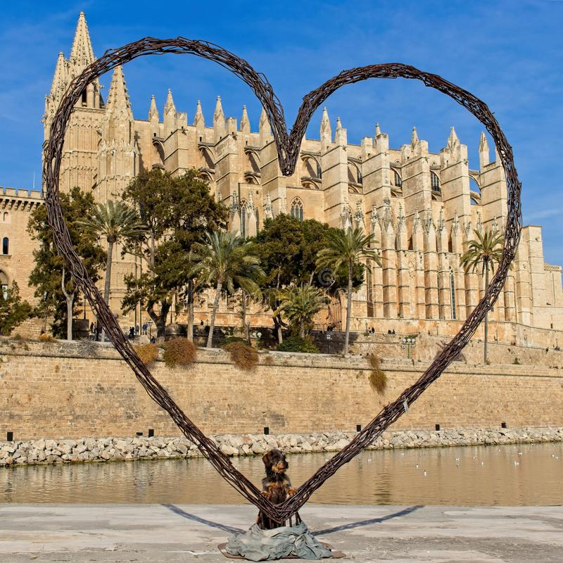 Palma cathedral with dachshund teckel dog posing for photograph inside large heart, palma, mallorca, spain. Palma cathedral with cute dachshund teckel dog posing royalty free stock images