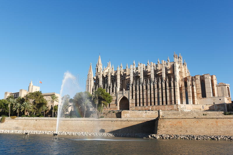 Palma cathedral with fountain, Majorca, Balearic Islands, Spain. Pond with fountain, clear blue sky. Afternoon, wide angle lens stock image