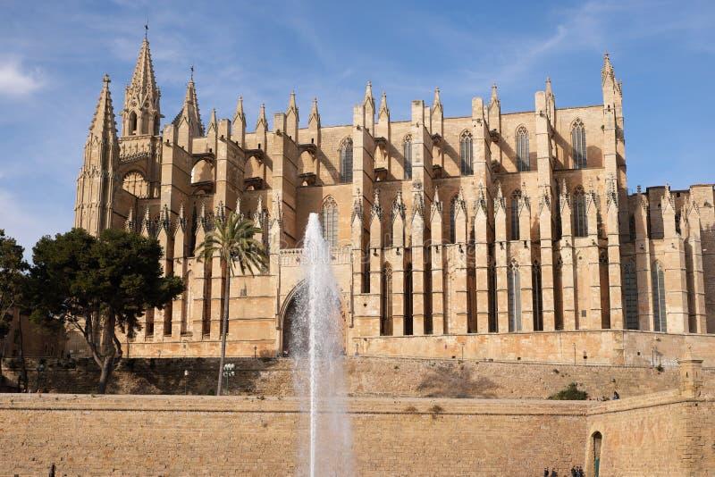 Palma de Mallorca, Espanha - 24 de março de 2019: vista lateral da catedral gótico famosa Santa Maria La Seu com lago e fonte den imagens de stock