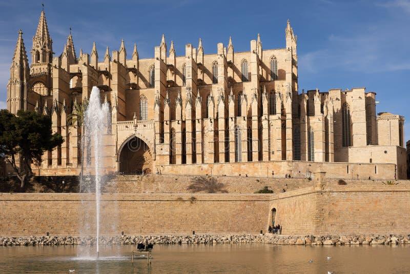 Palma de Mallorca, Espanha - 24 de março de 2019: vista lateral da catedral gótico famosa Santa Maria La Seu com lago e fonte imagem de stock